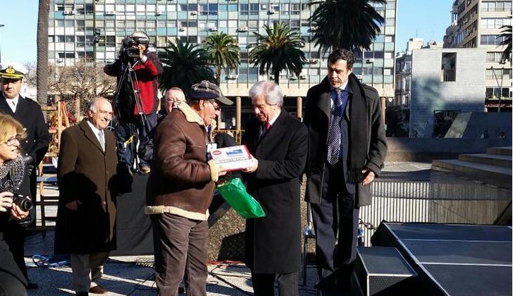 Momento de la entrega de la primera tablet a un adulto mayor, hoy durante la celebración del natalicio de José Artigas, en Plaza Independencia. Foto: Twitter @SCpresidenciauy.
