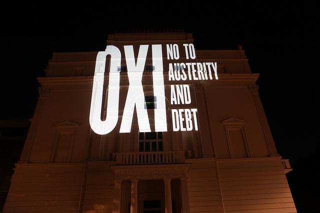 """""""όχι"""" (no en griego) fue la consigna de los que protestaban contra las medidas de la Eurozona. """"No a la austeridad y al débito"""", reza un anuncio luminoso sobre un edificio en Atenas, Grecia. Foto: Global Justice Now."""