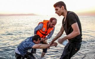 Un refugiado sirio exhausto es ayudado por voluntarios de una ONG, al llegar después de haber cruzado el Mar Egeo. Foto: Freedom House.