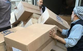 Voluntarios de ACNUR, la agencia de la ONU para refugiados, reparten cajas con ayuda humanitaria de todo tipo. Foto: ACNUR.