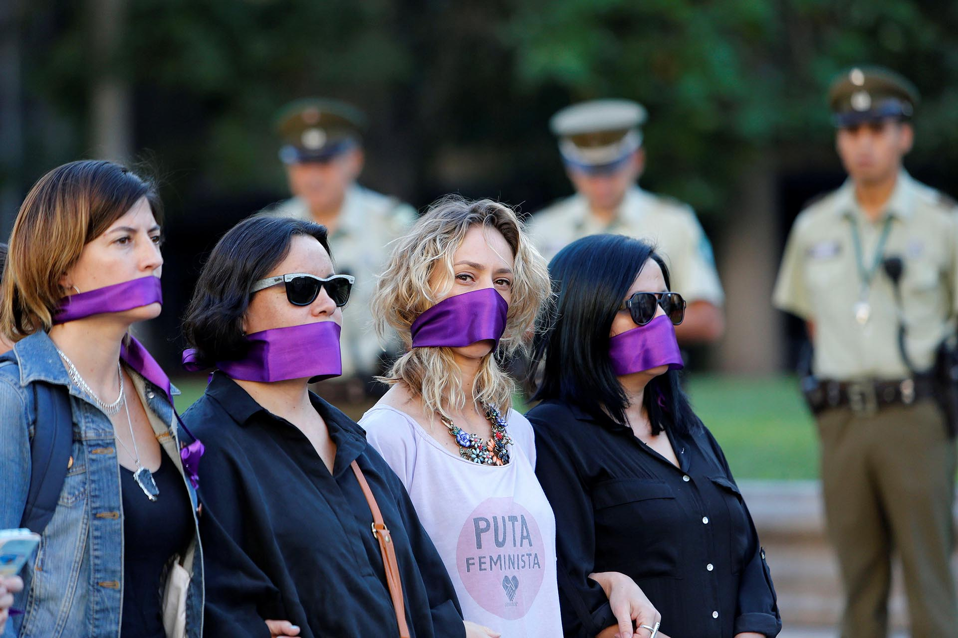 Women cover their mouths as they attend a peaceful demonstration in front of the government house as part of International Women's Day, in Santiago, Chile March 8, 2017. REUTERS/Carlos Vera EDITORIAL USE ONLY. NO RESALES. NO ARCHIVE