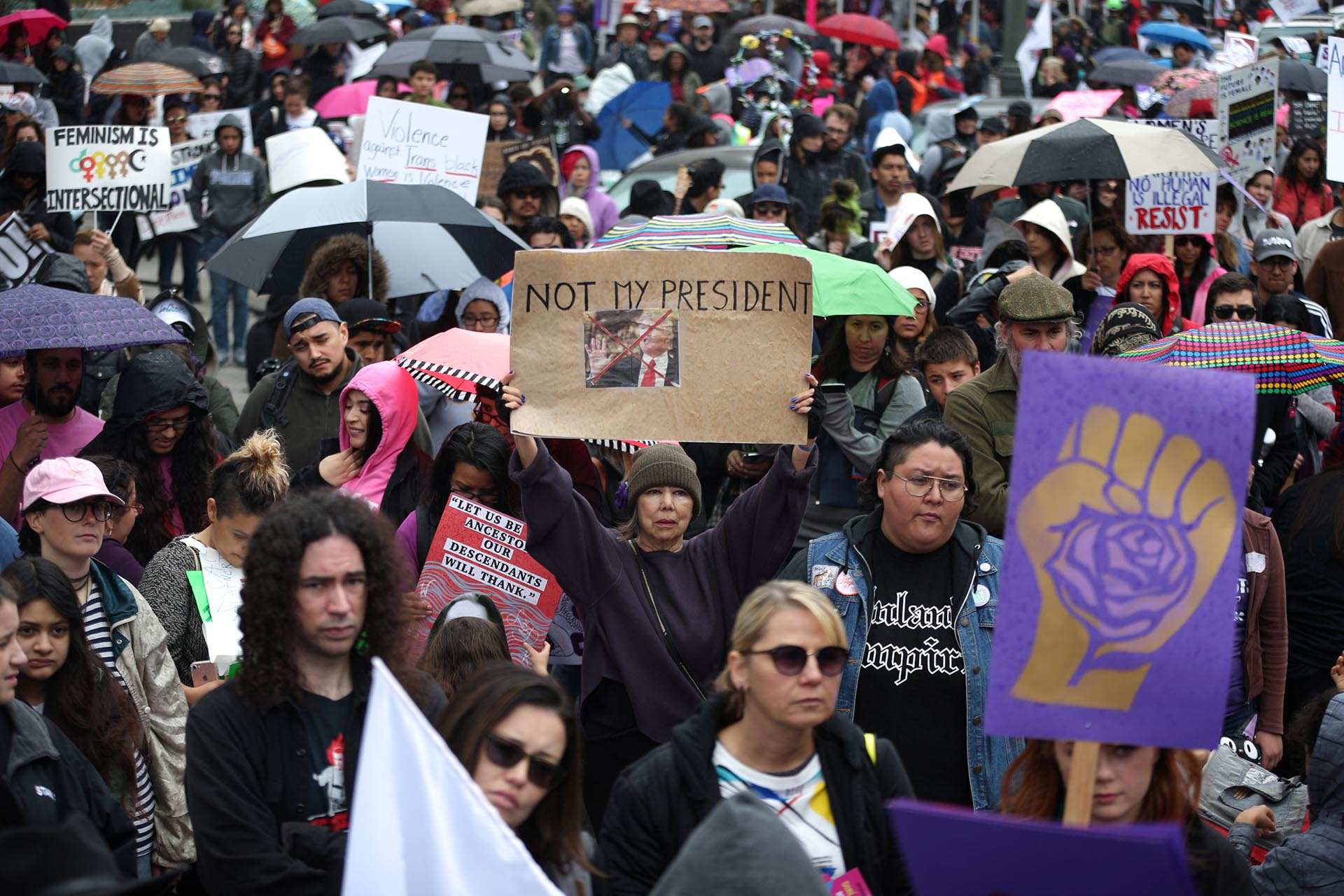 People listen to speakers in the rain at a rally for International Women's Day in Los Angeles, California, U.S., March 5, 2017. REUTERS/Lucy Nicholson
