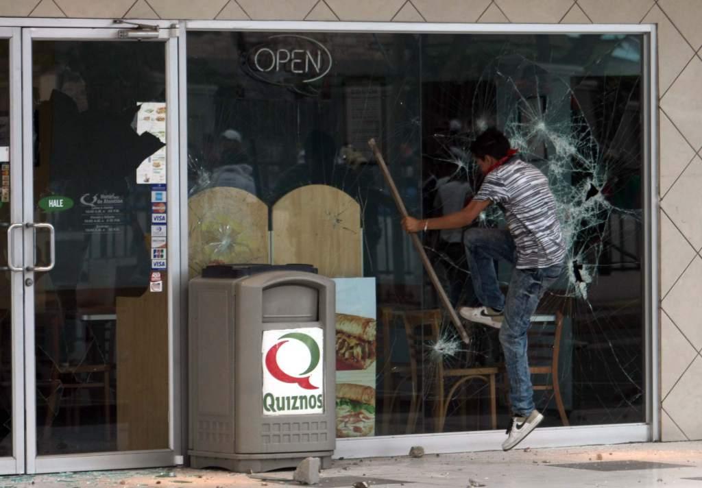 Un joven con su cara tapada patea la puerta de un local de comidas rápidas. Foto cortesía de laprensa.hn