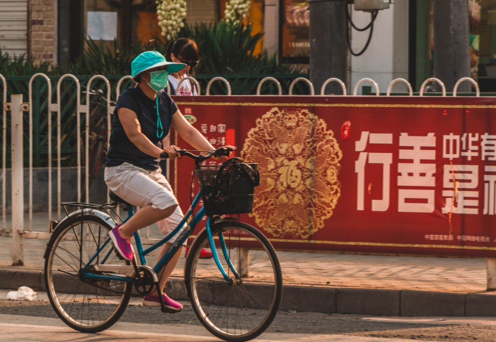 Una mujer transita en bicicleta por Beijing mientras usa un barbijo para evitar inhalar smog. Foto: Pixabay