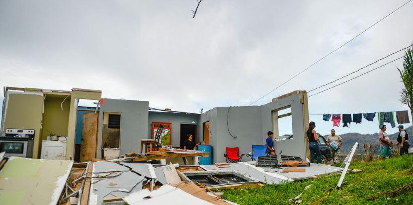 Una familia de Utuado, Puerto Rico, reciben agua y comida mientras se refugian en el único cuarto de su casa que quedó en pie tras el paso del huracán María. Foto: USDA/Flickr