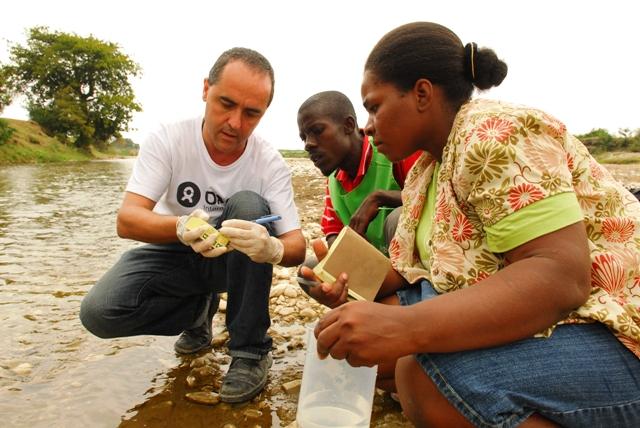 Funcionarios de OXFAM revisan un río para verificar la calidad del agua. Foto: Oxfam Internacional