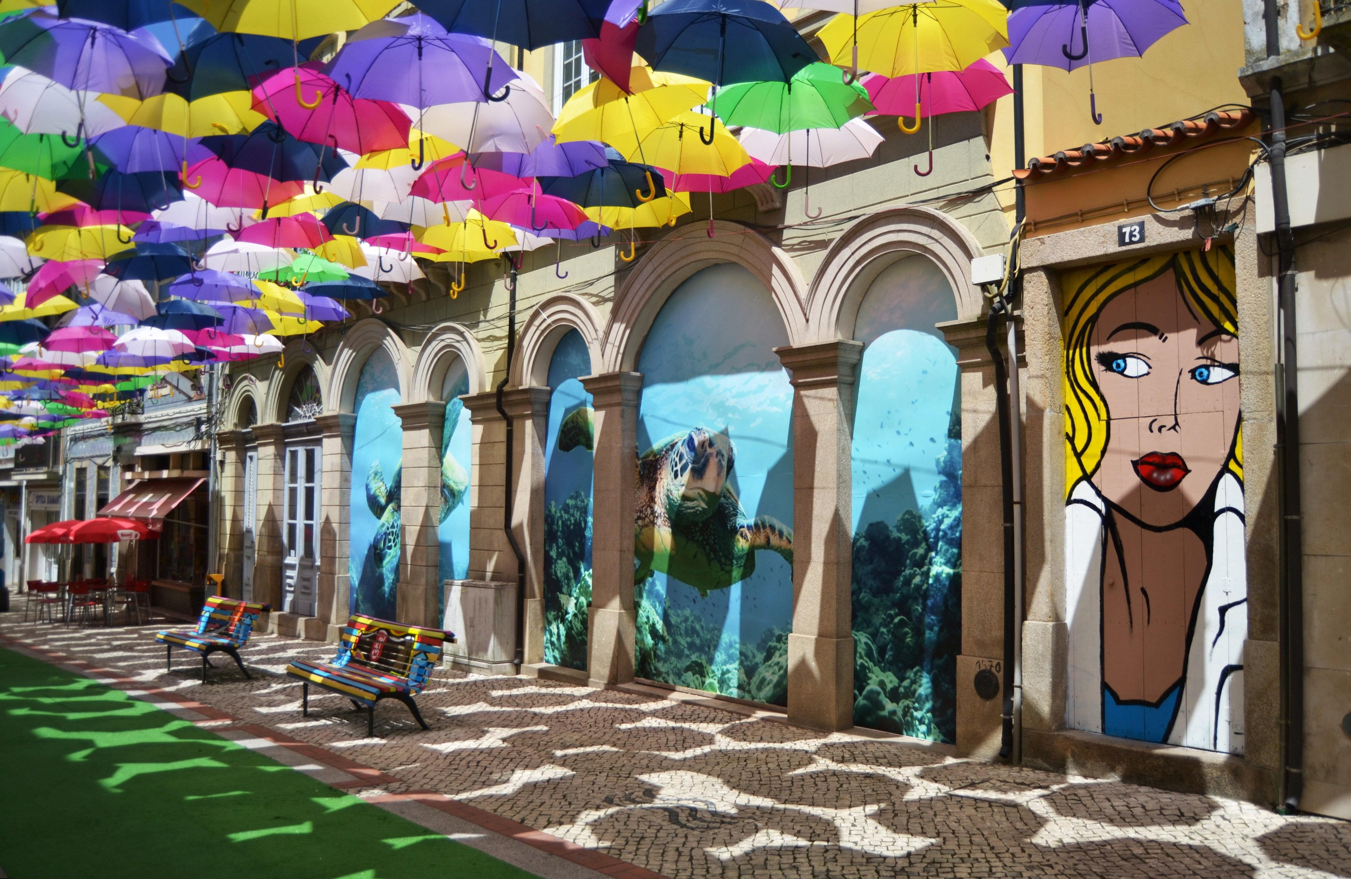 GRA029. ÁGUEDA (PORTUGAL), 06/08/2014.- Fotografía facilitada por la empresa Sextafeira, de una calle de la pequeña localidad de Águeda, en el interior de Portugal, invadida de color en forma de paraguas flotantes, bancos pintados y grafitis en las paredes que atraen a miles de turistas a esta ciudad, revivida con un proyecto de arte urbano de bajo coste. La iniciativa surgió del consistorio que buscaba dar respuestas a las quejas de comerciantes en el centro histórico tras haber perdido clientes por la peatonalización de varias calles. EFE/ ***SOLO USO EDITORIAL***