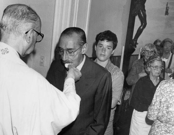 En esta fotografía de archivo se ve cómo el dictador Jorge Videla recibe la comunión de un sacerdote local