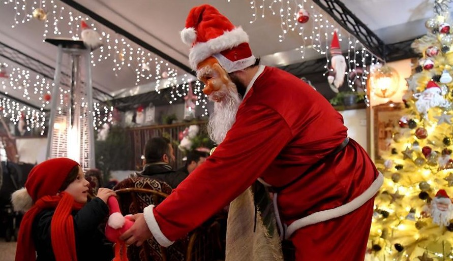 Una persona vestida como Santa Claus le da un regalo a un niño en un restaurante en la ciudad de Aleppo, al norte de Siria, el 18 de diciembre de 2018. Foto: Xinhua / Ammar Safarjalani