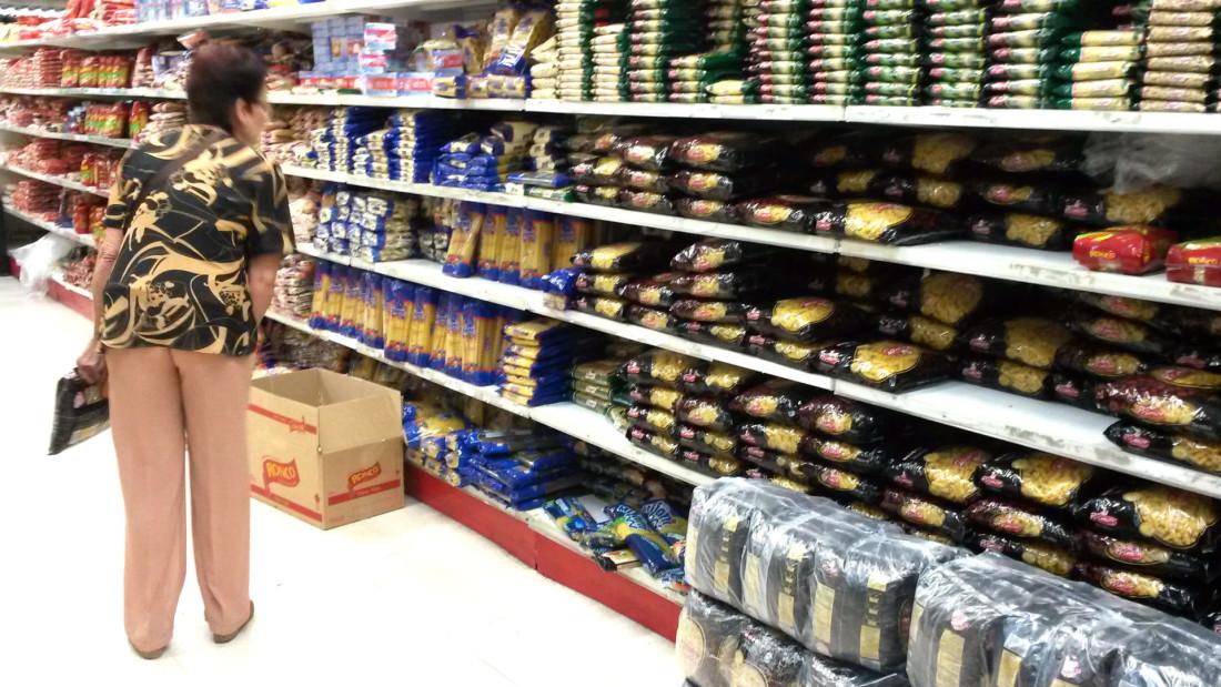 Una mujer observa los precios de alimentos básicos en un supermercado de Caracas. Foto: cortesía de VPI