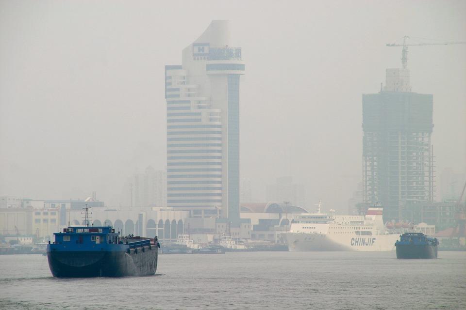 Barios barcos navegan por el río Yangtsé, en Shanghai, China. Atrás una densa cortina de smog nubla la ciudad. Foto: Pixabay
