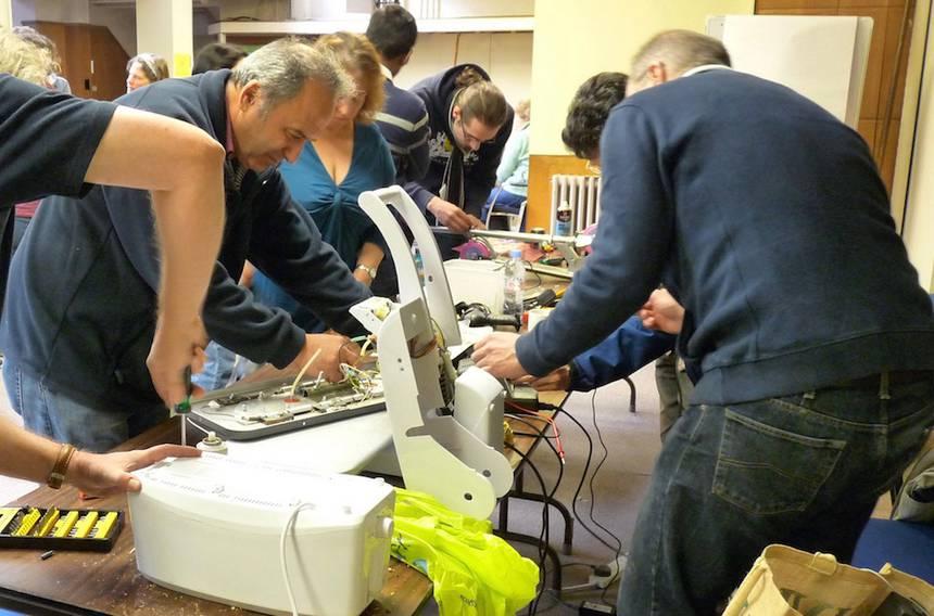 """Varias personas reparan electrodomésticos en el """"Repair Cafe"""", en Reading, Reino Unido. Foto: Wikimedia Commons"""