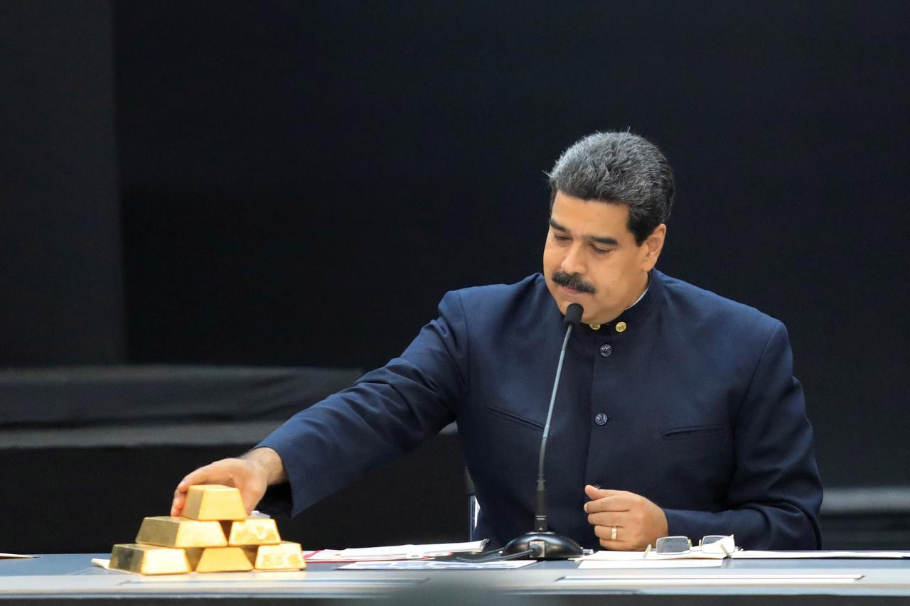 Nicolás Maduro toca unos lingotes de oro, en una reunión con ministros del área económica, en el Palacio de Miraflores (Caracas), en marzo de 2018. Foto: REUTERS/Marco Bello