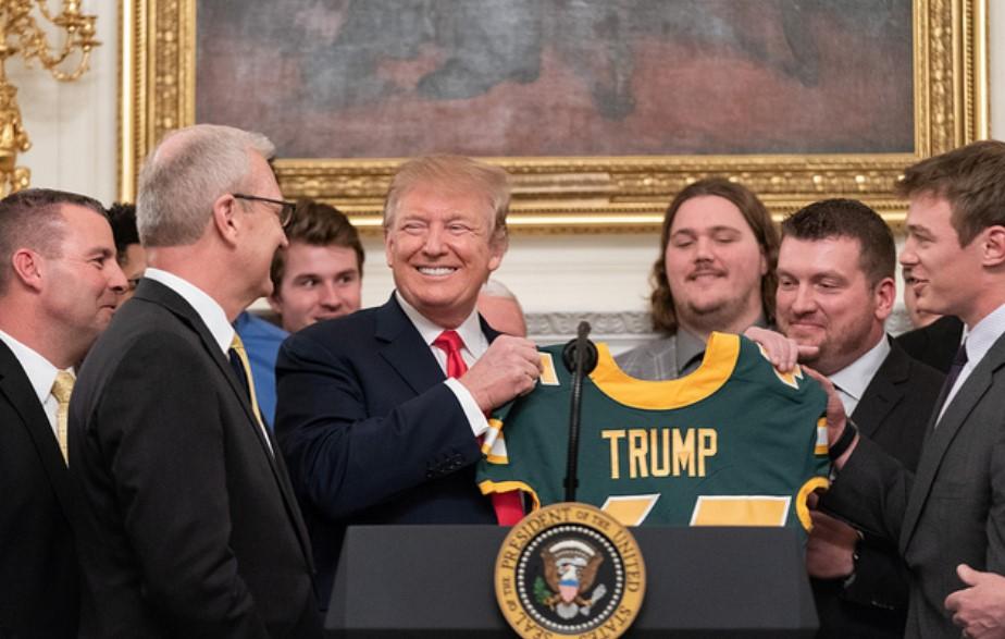 Trump sostiene una camiseta de un equipo de fútbol americano con su nombre. Foto: The White House