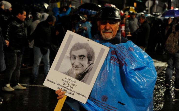 Hombre bajo la lluvia reclama por un desaparecido / Foto: Presidencia