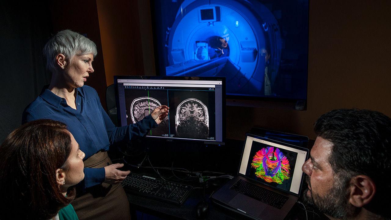 Leanne Williams (de pie) y su compañera de psiquiatría Laura Hack revisan los escáneres cerebrales de Moe mientras él observa. Foto: Lipo Ching