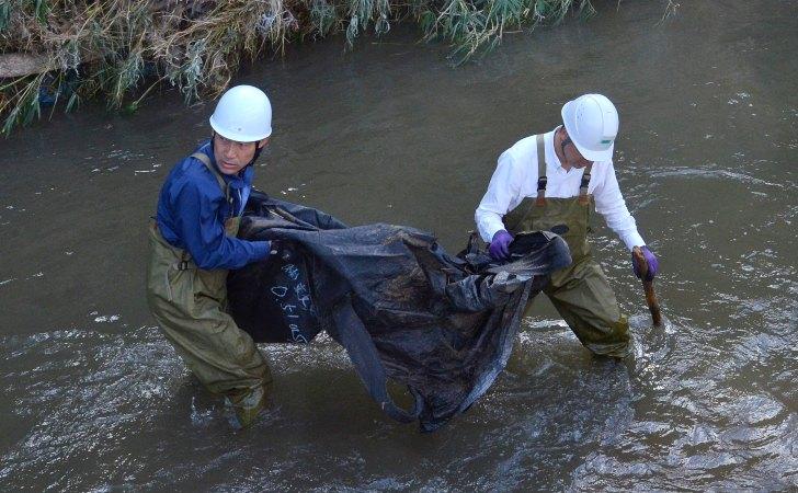 Trabajadores nipones retiran una bolsa de desechos radiactivos vacía del río / Foto: Hideyuki Miura