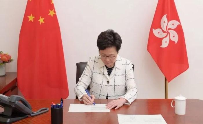Carrie Lam firma la ley en nombre del gobierno de Hong Kong. Foto: Gobierno de Hong Kong
