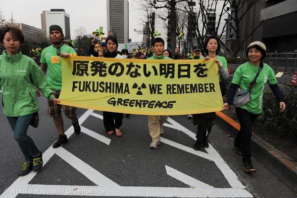 Manifestantes de Greenpeace portan un cartel en protesta al manejo del desastre de Fukushima por parte del Estado japonés
